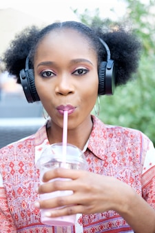 オープンエアのカフェに座って、音楽を聴いて、牛乳のカクテルを飲んでヘッドフォンで民族衣装で黒アフロガール