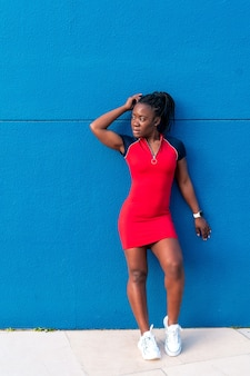 Black afro girl posing in the street on a blue background in a colourful red dress