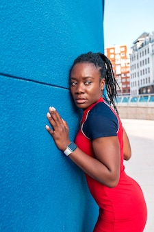 Black afro girl posing in the street with her hands on a blue wall wearing a colourful red dress