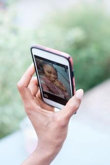 スマートフォンを押しながら自分撮りを作る黒のアフロガールの手