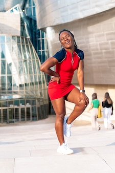 Black afro girl smiling posing on the street of a modern city in a colourful red dress