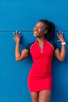 Black afro girl smiling posing in the street with her hands on a blue wall wearing a colourful red dress