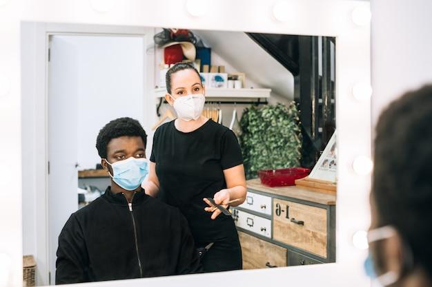 코로나 바이러스에서 얼굴에 마스크를 쓰고 이발소에서 머리를 자르는 흑인 아프리카 남자 미용사가 그에게 뭔가를 설명하고 거울에 반영됩니다.