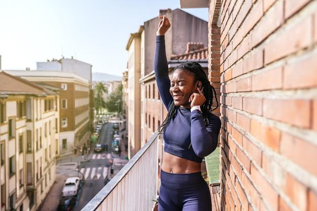 Черная афро-женщина, одетая в спортивную одежду, слушает музыку в наушниках, очень счастлива на балконе, потому что она собирается начать заниматься дома из-за пандемии коронавируса covid19
