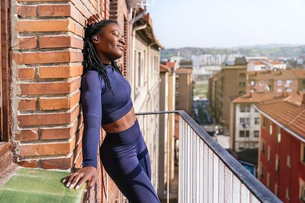 Черная афро женщина, одетая в спортивную одежду, слушает музыку в наушниках, очень счастлива на балконе своего дома, потому что она собирается начать заниматься дома из-за пандемии коронавируса covid19
