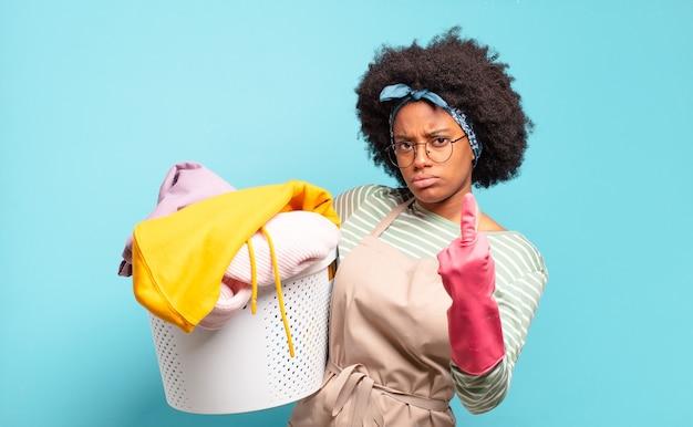 흑인 아프리카 여성은 화가 나고 짜증이 나고 반항적이고 공격적이며 가운데 손가락을 뒤집고 반격합니다. 가사 개념 .. 가정 개념