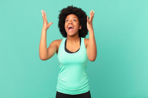 흑인 아프리카 여성은 행복하고, 놀라고, 운이 좋고 놀라며 두 손을 위로 들고 승리를 축하합니다.