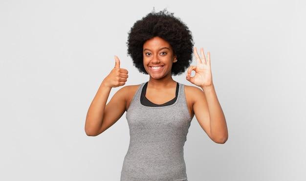 幸せ、驚き、満足、驚きを感じ、大丈夫と親指を立てるジェスチャーを示し、笑顔の黒人のアフロ女性 Premium写真