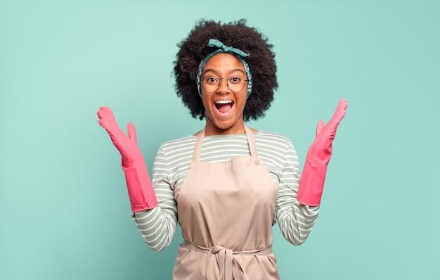 Черная афро-женщина чувствует себя счастливой, взволнованной, удивленной или шокированной, улыбается и удивляется чему-то невероятному. концепция домашнего хозяйства .. концепция домашнего хозяйства
