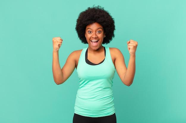 흑인 아프리카 여성은 행복하고 놀라고 자랑스러워하며 큰 미소를 지으며 성공을 축하합니다