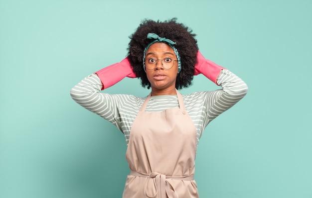 ストレス、心配、不安、恐怖を感じ、頭に手を当てて、誤ってパニックに陥った黒人のアフロ女性。ハウスキーピングのコンセプト..家庭のコンセプト