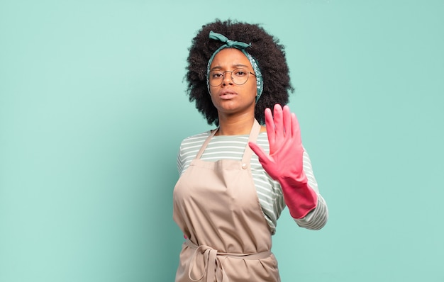 Black afro woman looking serious, stern, displeased and angry showing open palm making stop gesture. housekeeping concept. household concept