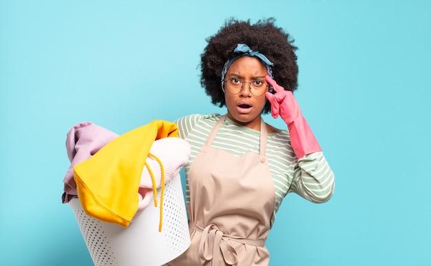 Черная афро женщина выглядит удивленной, с открытым ртом, шокированной, осознающей новую мысль, идею или концепцию. концепция домашнего хозяйства .. концепция домашнего хозяйства