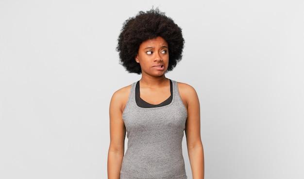 걱정하고, 스트레스 받고, 불안하고, 무서워하고, 당황하고 이를 악물고 있는 흑인 아프리카 여성