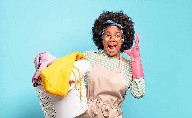 Black afro woman screaming with hands up in the air, feeling furious, frustrated, stressed and upset. housekeeping concept