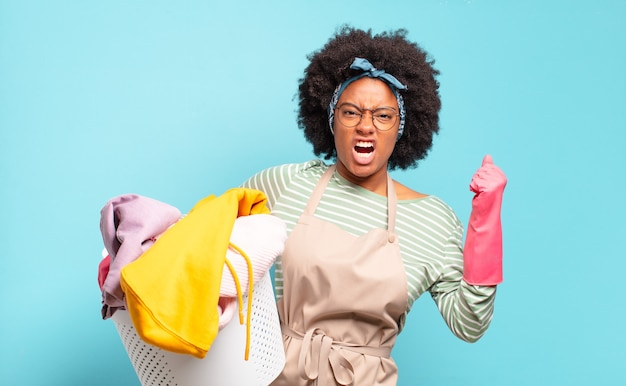 Black afro woman shouting aggressively with an angry expression or with fists clenched celebrating success. housekeeping concept.. household concept