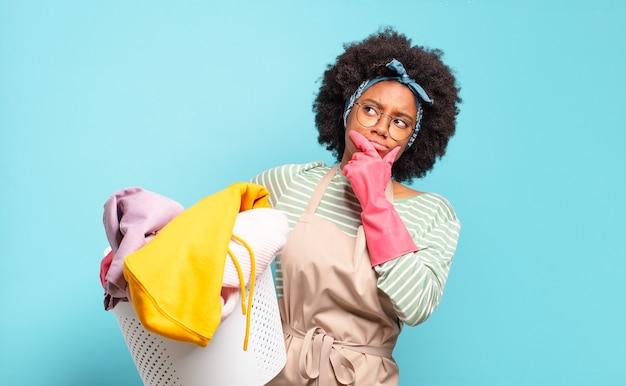 Черная афро женщина думает, чувствует себя сомнительно и смущенно, с разными вариантами, гадая, какое решение принять. концепция домашнего хозяйства .. концепция домашнего хозяйства