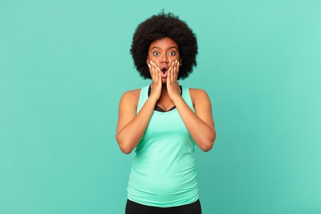 Черная афро женщина в фитнес-одежде у изолированной стены