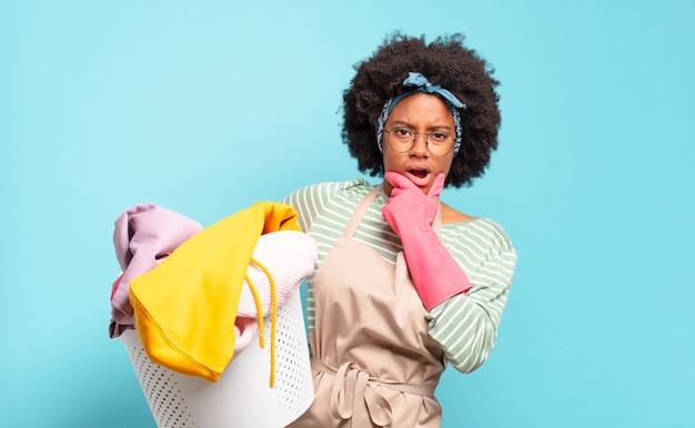 Черная афро-женщина с широко открытыми глазами и ртом, положив руку на подбородок, чувствуя неприятный шок, говорит что или ничего себе.