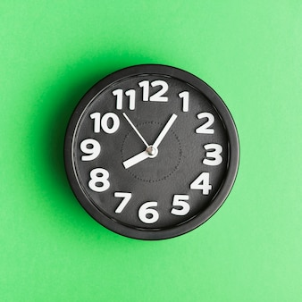 Black alarm clock against green background