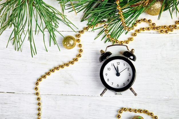黒の目覚まし時計とモミの木の枝
