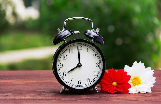 テーブルの上の黒い目覚まし時計と夏の花。