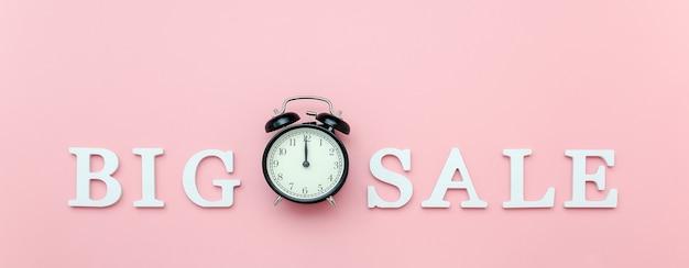 ピンクの白いボリューム文字から黒の目覚まし時計とテキストビッグセール