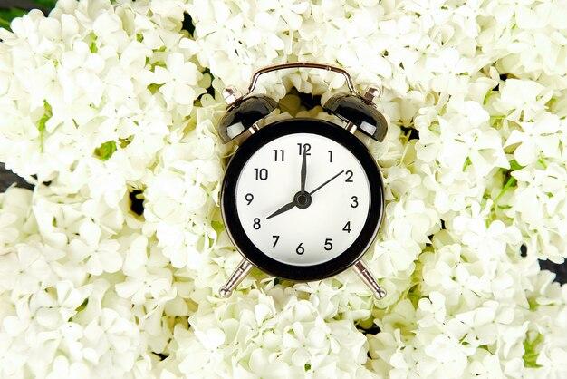 Черный будильник и белые цветы