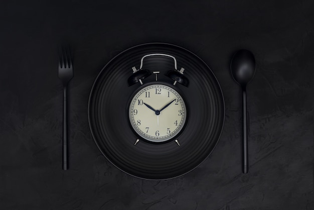 Black alarm clock on black plate with spoon and fork on black background. black monochrome concept.