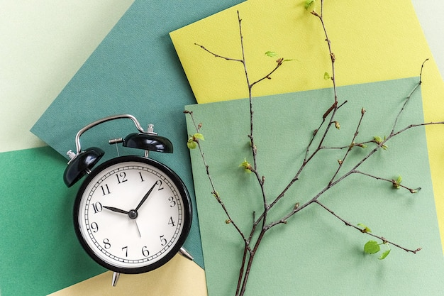 Black alarm clock and branches of tree with young blossoming leaves on geometric green shades background.