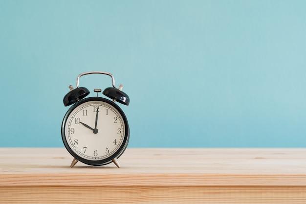 Black alarm clock on brown wood desk and blue