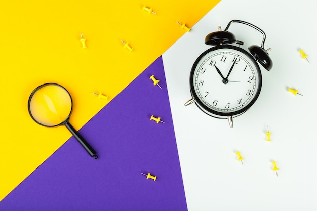 Black alarm clock on color block background