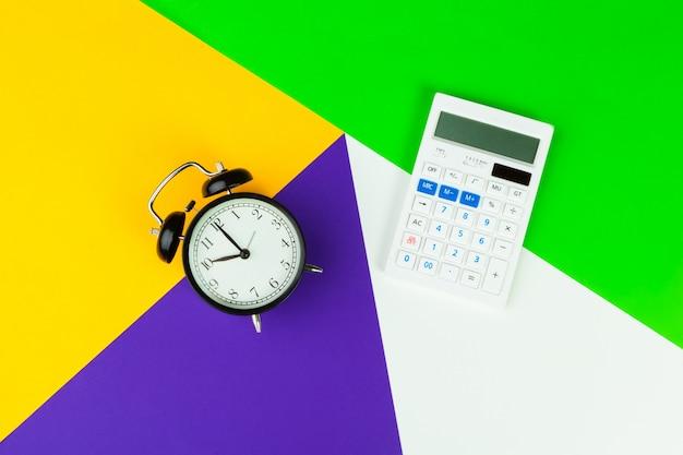 Black alarm clock on color block, office interior