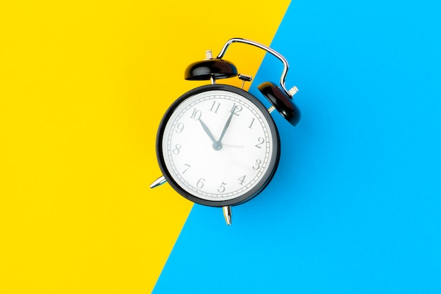 Black alarm clock on color block yellow and blue