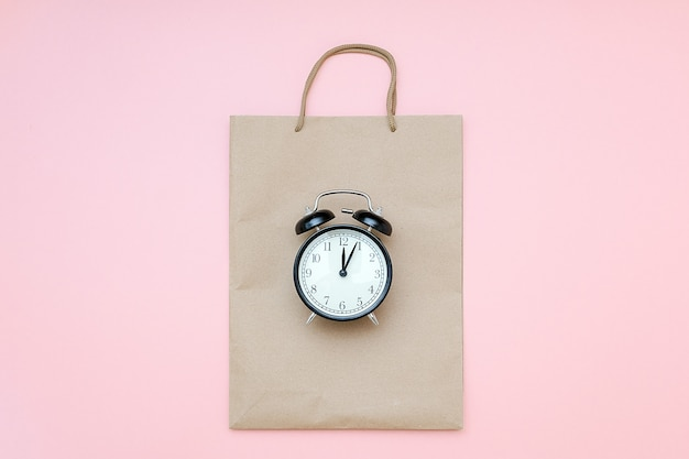 Black alarm clock on craft package on a pink background. concept black friday , season sales time