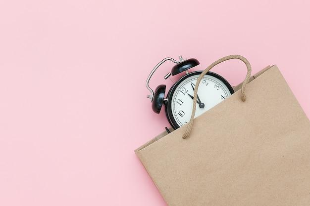 Black alarm clock in craft package on pink
