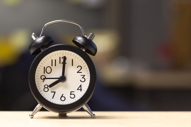 Black alarm clock on desk table