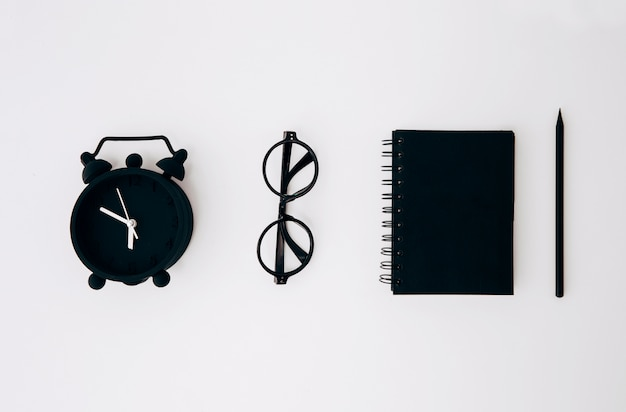 Black alarm clock; eyeglasses; closed diary and pencil on white background