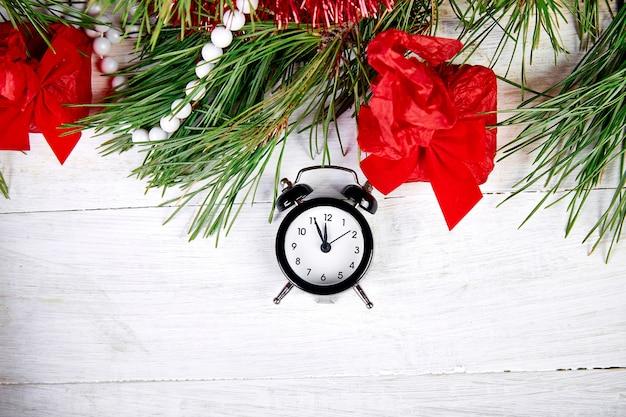 Black alarm clock and fir tree branch