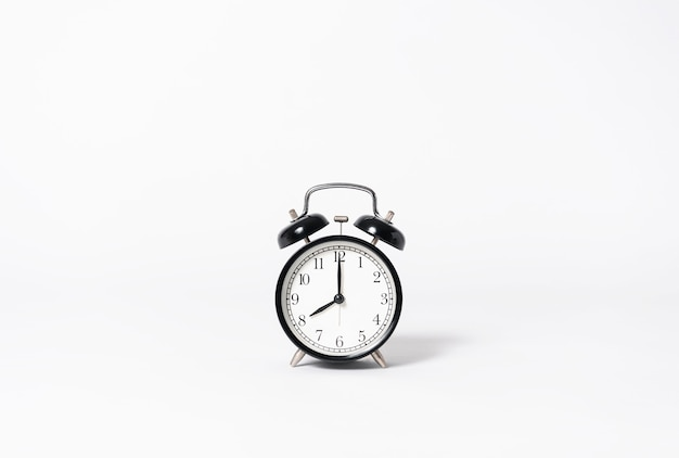 Black alarm clock on gray background. minimal object creative idea.