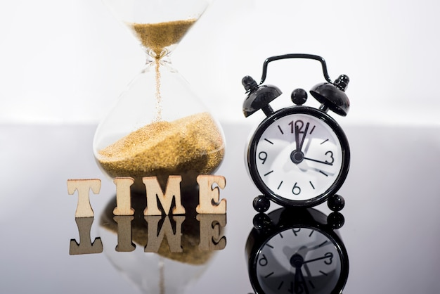 Black alarm clock and hourglass