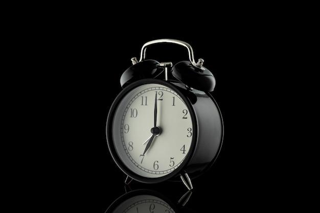 黒の背景に分離された黒の目覚まし時計。