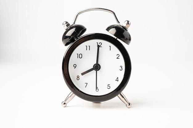 白い背景で隔離の黒の目覚まし時計。
