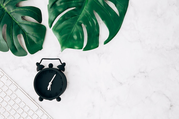 Black alarm clock; keyboard and green monstera leaves on white marble background