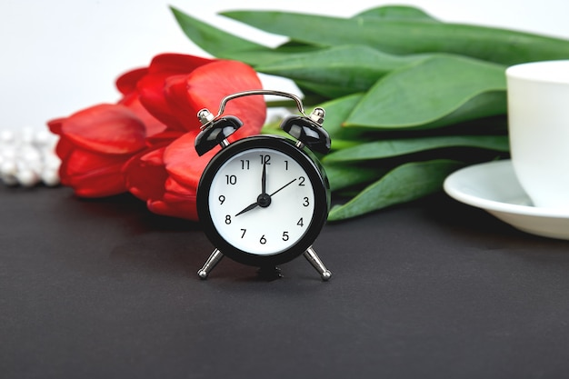 Black alarm clock near bouquet red tulips and cup of lemon tea mother or woman  day. greeting card. good morning breakfast. copy space. spring.