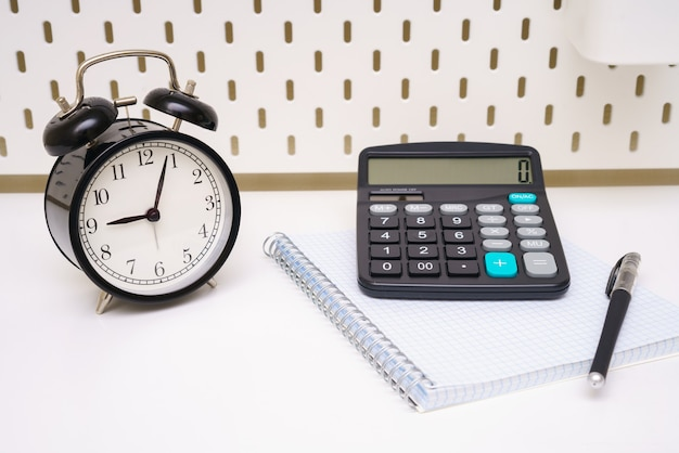 A black alarm clock notepad pen and calculator are placed on a white background of the table five mi...