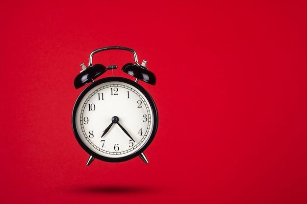 빨간색 배경에 검은 색 알람 시계입니다. 창의적인 구성.