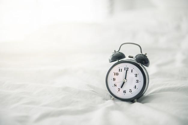 日光と朝のベッドの上の黒の目覚まし時計