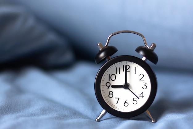 ベッドの上の黒い目覚まし時計