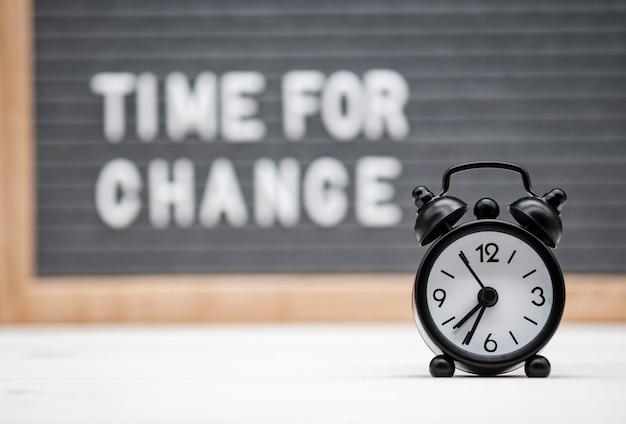 변화를위한 비문 시간의 배경에 검은 색 알람 시계